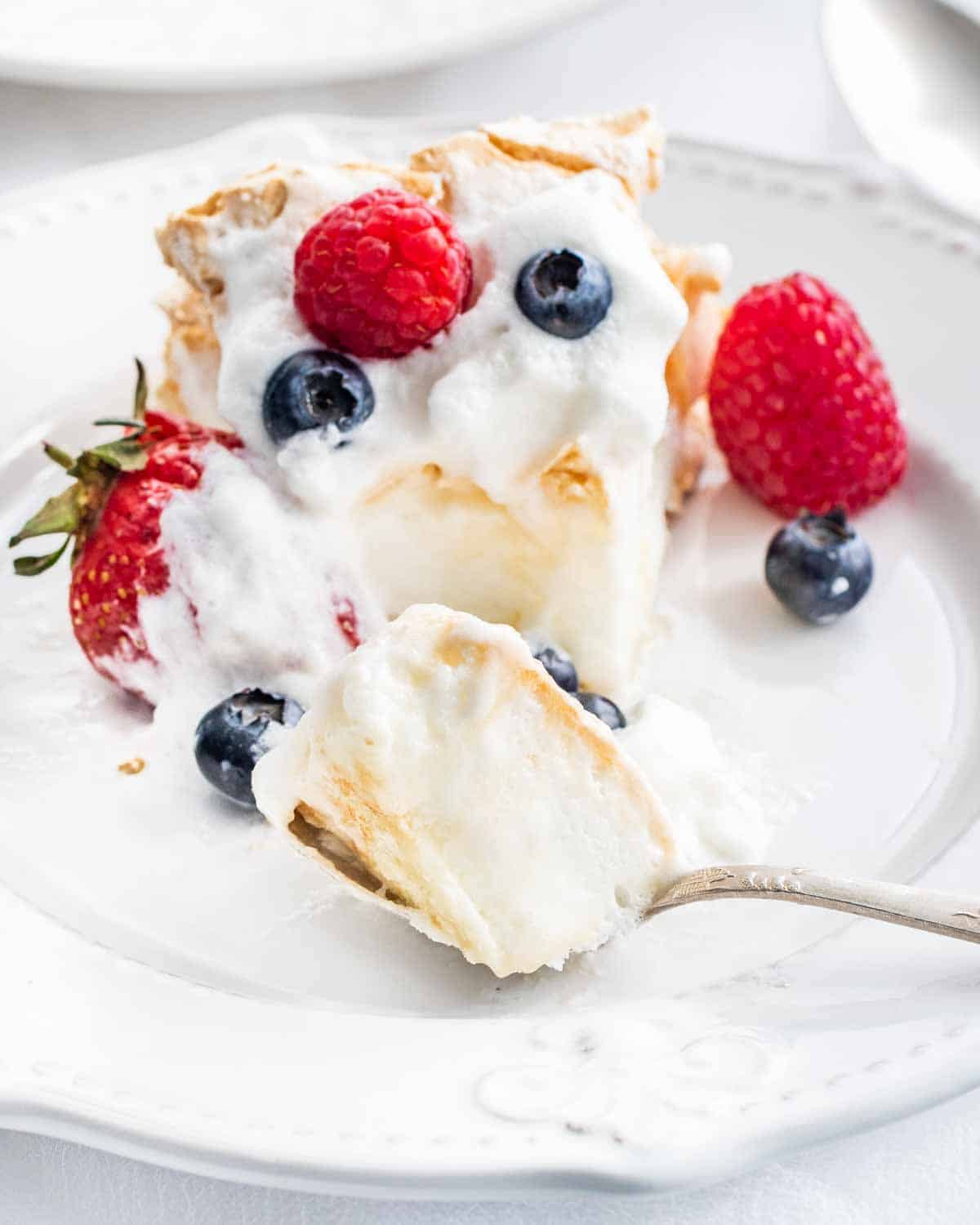 a slice of pavlova on a plate garnished with berries and a spoon holding a piece of it