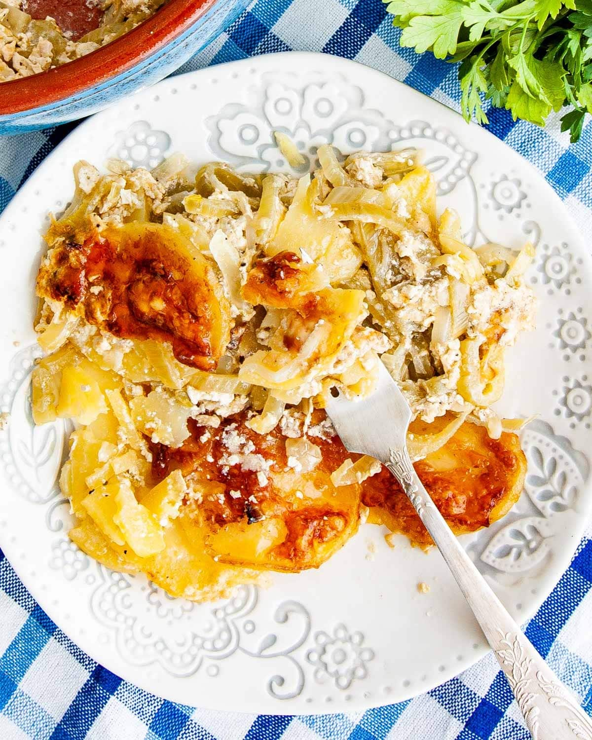 overhead shot of fennel potato gratin on a white plate with a fork in it