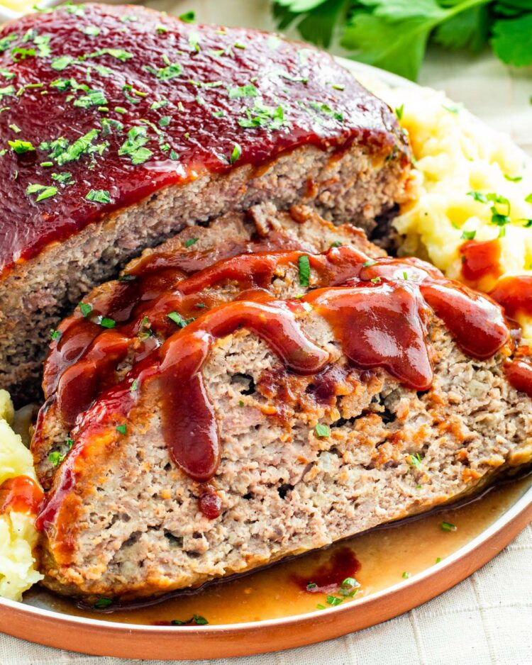 sideview shot of sliced meatloaf with mashed potatoes on a serving platter