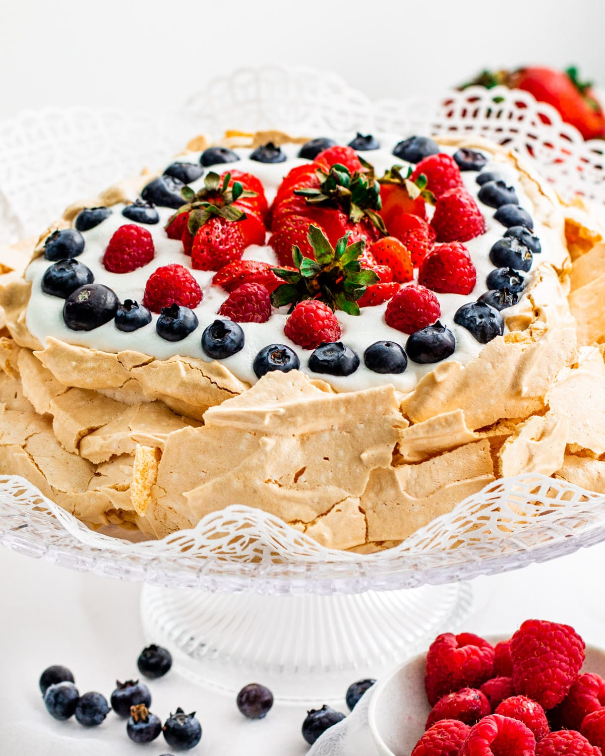 a gorgeous pavlova on a cake plate topped with whipped cream and berries