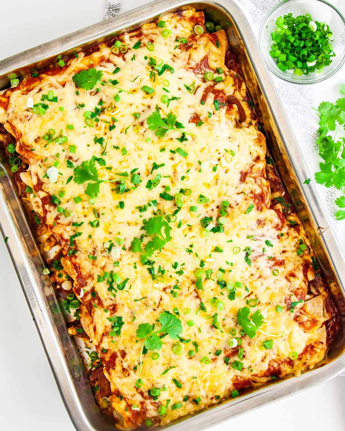 overhead shot of chicken enchiladas in a casserole dish garnished with cilantro and green onions