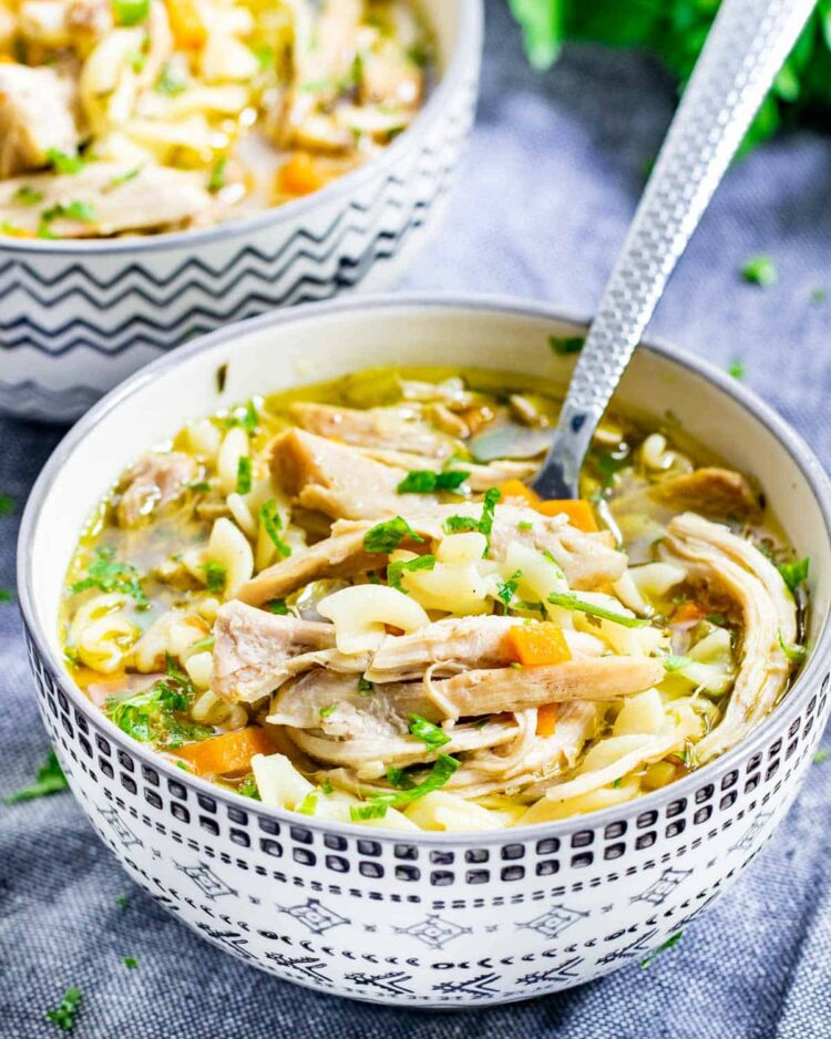 2 bowls full of chicken noodle soup with spoons inside