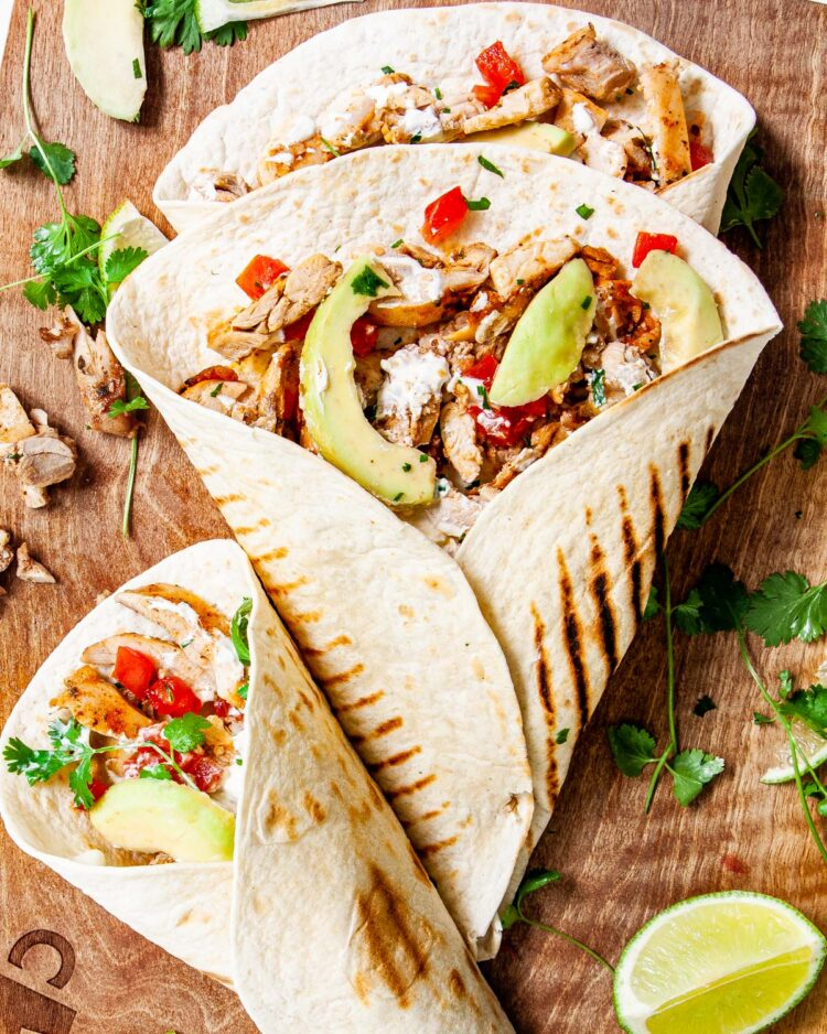 overhead shot of 3 chicken street tacos on a cutting board garnished with lime wedges and cilantro