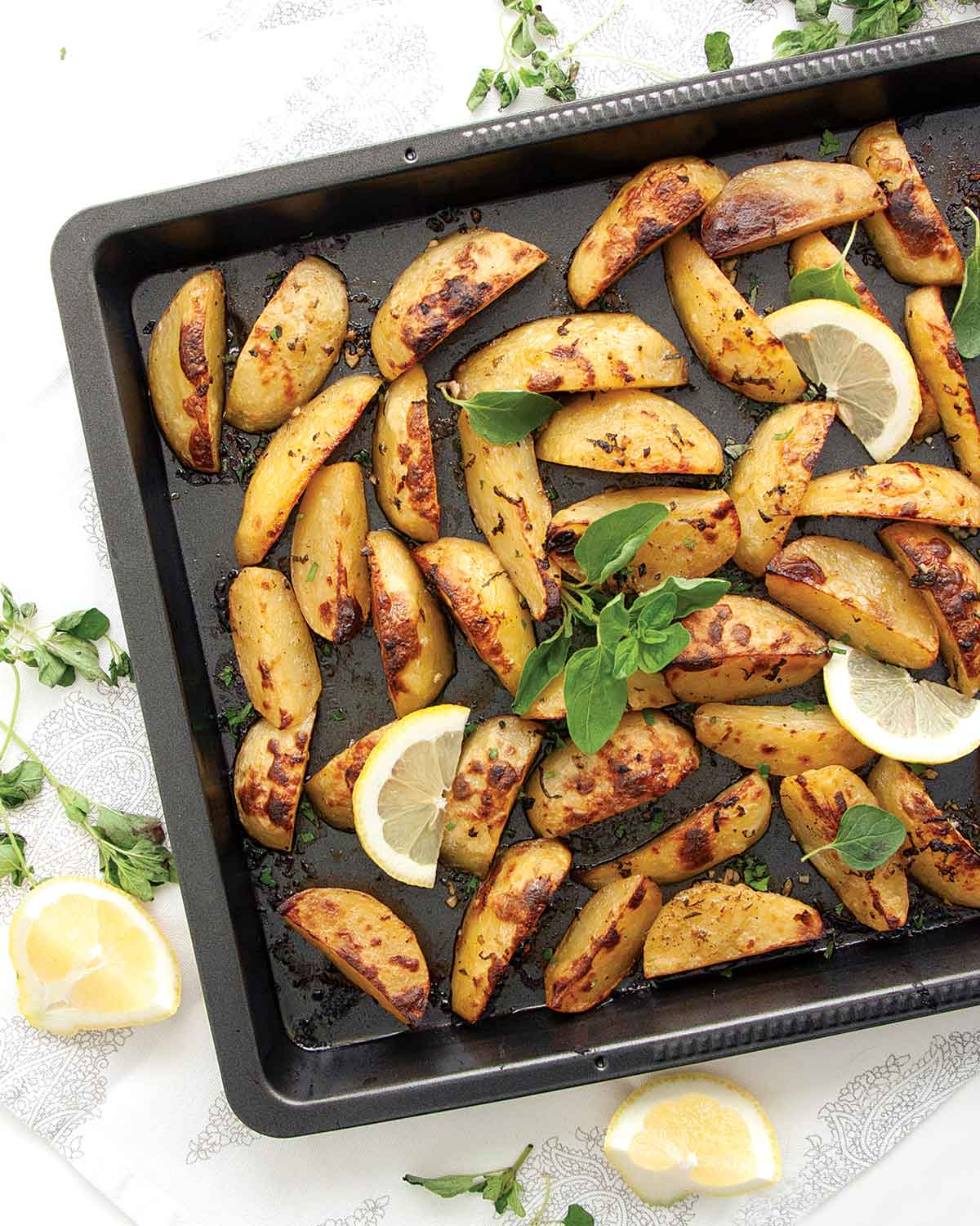 fresh out of the oven greek lemon potatoes on a baking sheet garnished with fresh oregano