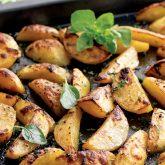 fresh out of the oven greek lemon potatoes on a baking sheet garnished with fresh oregano