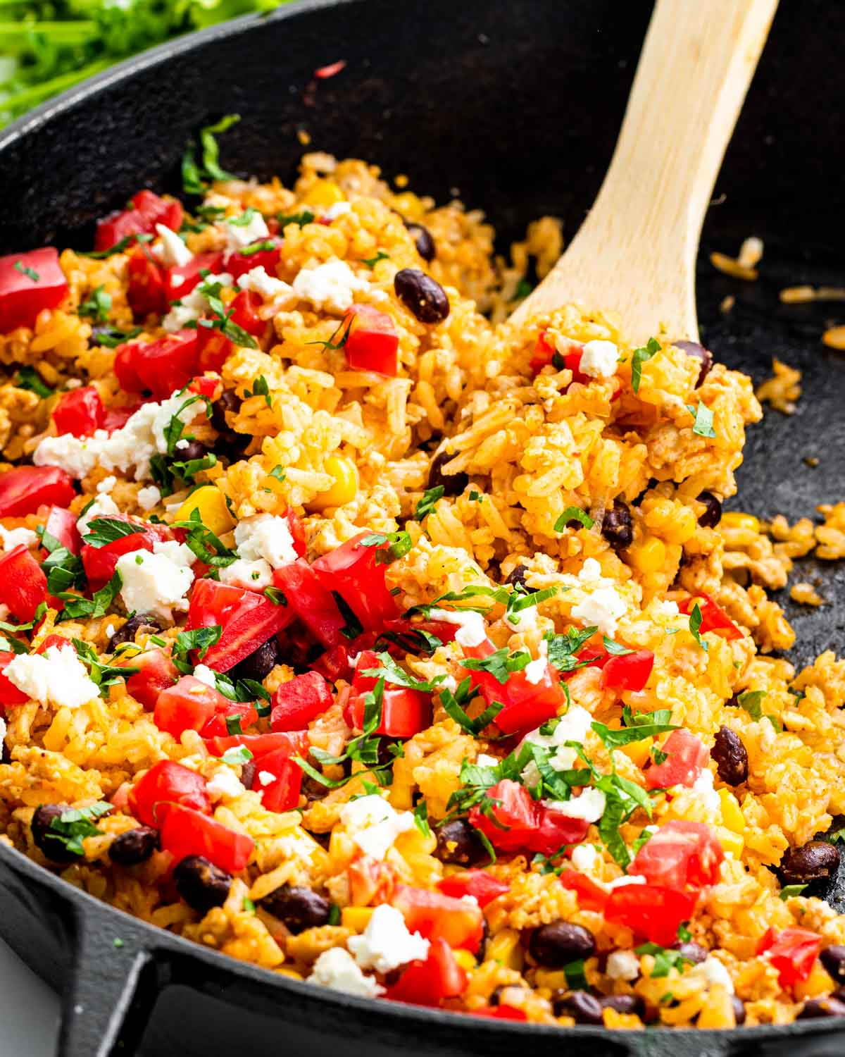 mexican fried rice in a skillet with a wooden spoon