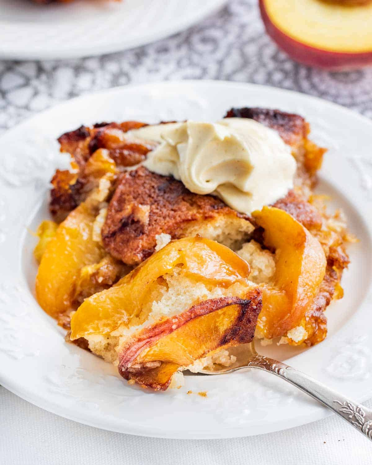 a piece of peach cobbler with a scoop of vanilla ice cream on a white plate with a spoon