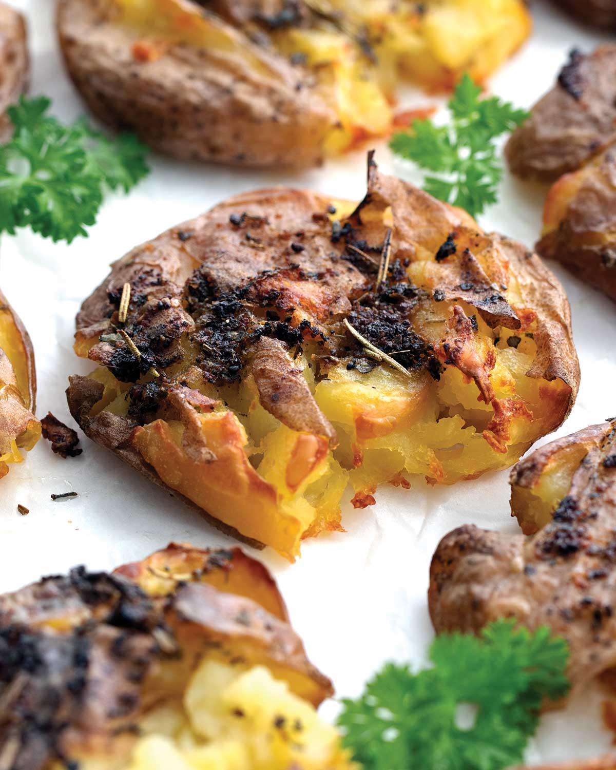 closeup of a smashed potato garnished with parsley