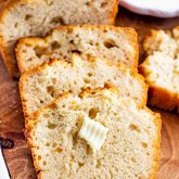 3 slices of honey beer bread on a cutting board with a pat of butter.