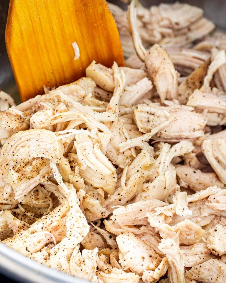 closeup of shredded chicken in the instant pot with a wooden spatula inside