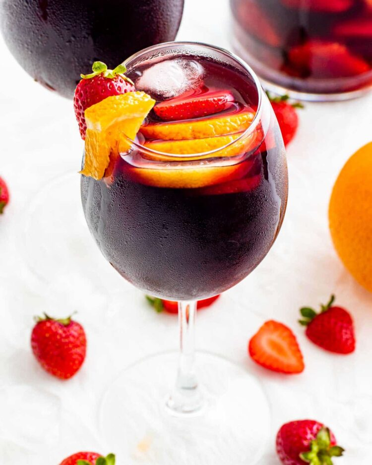 red sangria in a wine glass with fruits and ice cubes