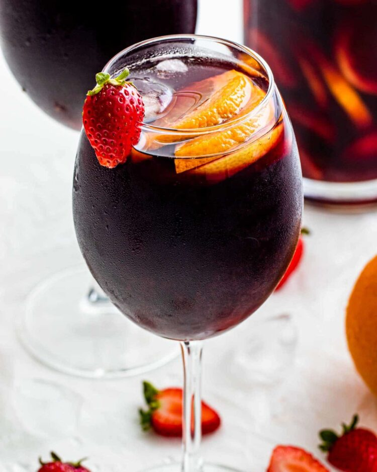 red sangria in a glass with a pitcher in the background