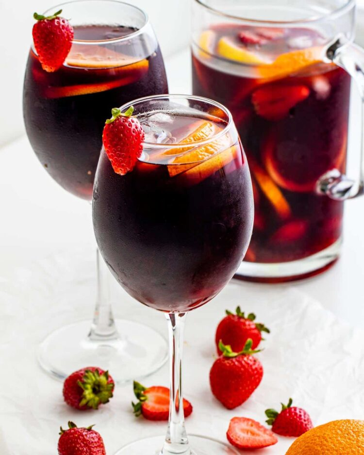 two glasses with red sangria and a pitcher in the background