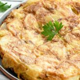 spanish tortilla on a plate with a garnish of parsley.