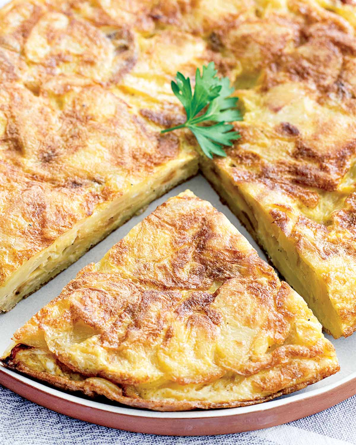 spanish tortilla on a plate with a slice cut out.