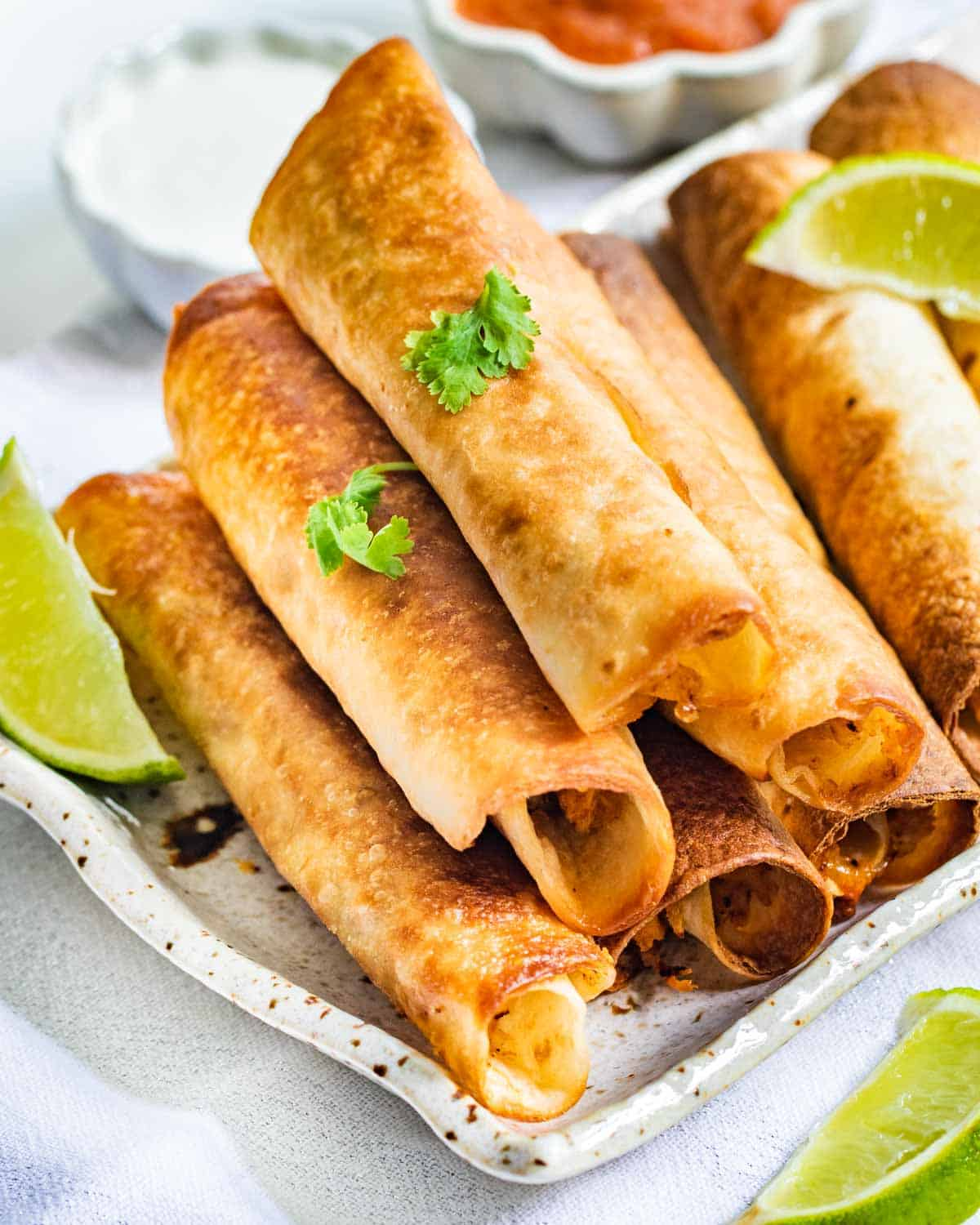 chicken taquitos stacked on top of each other on a serving platter.
