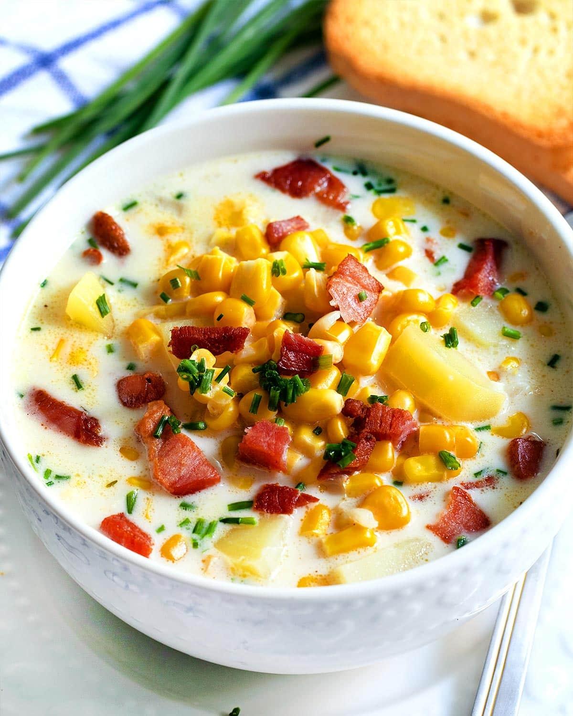 closeup of corn chowder in a white bowl.