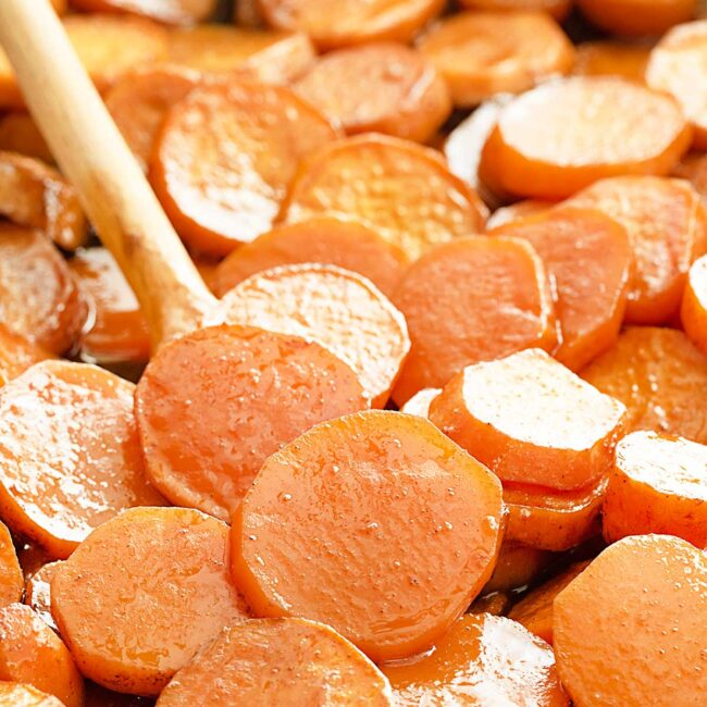 candied yams on a baking sheet with a wooden spoon.