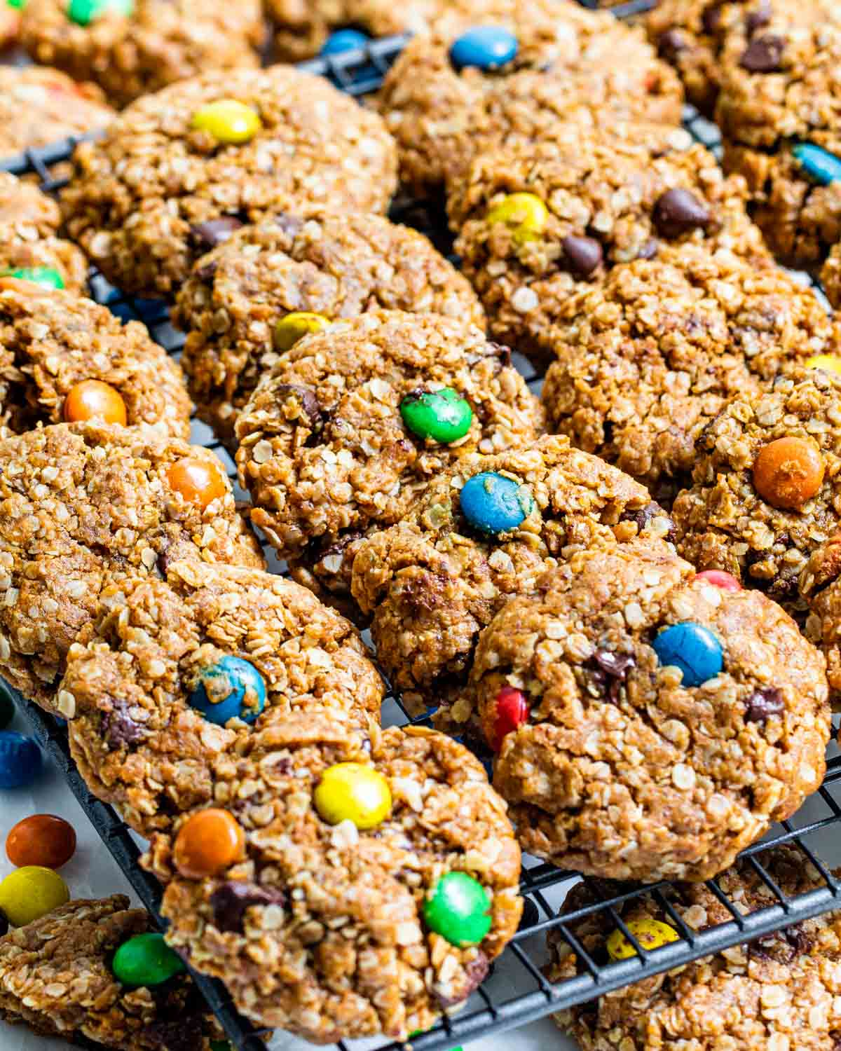 freshly baked monster cookies on a cooling rack.