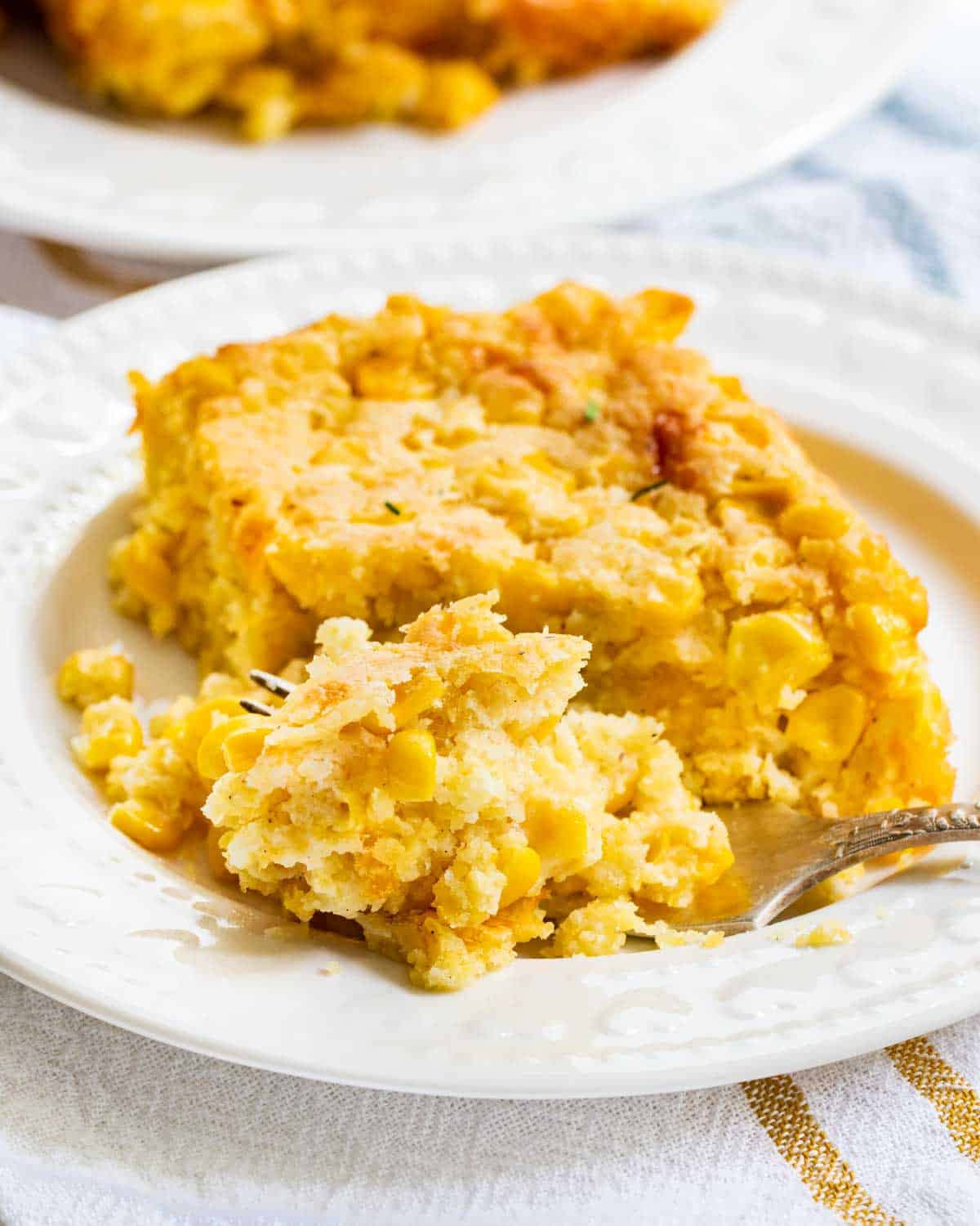 a slice of corn casserole on a plate with a fork.