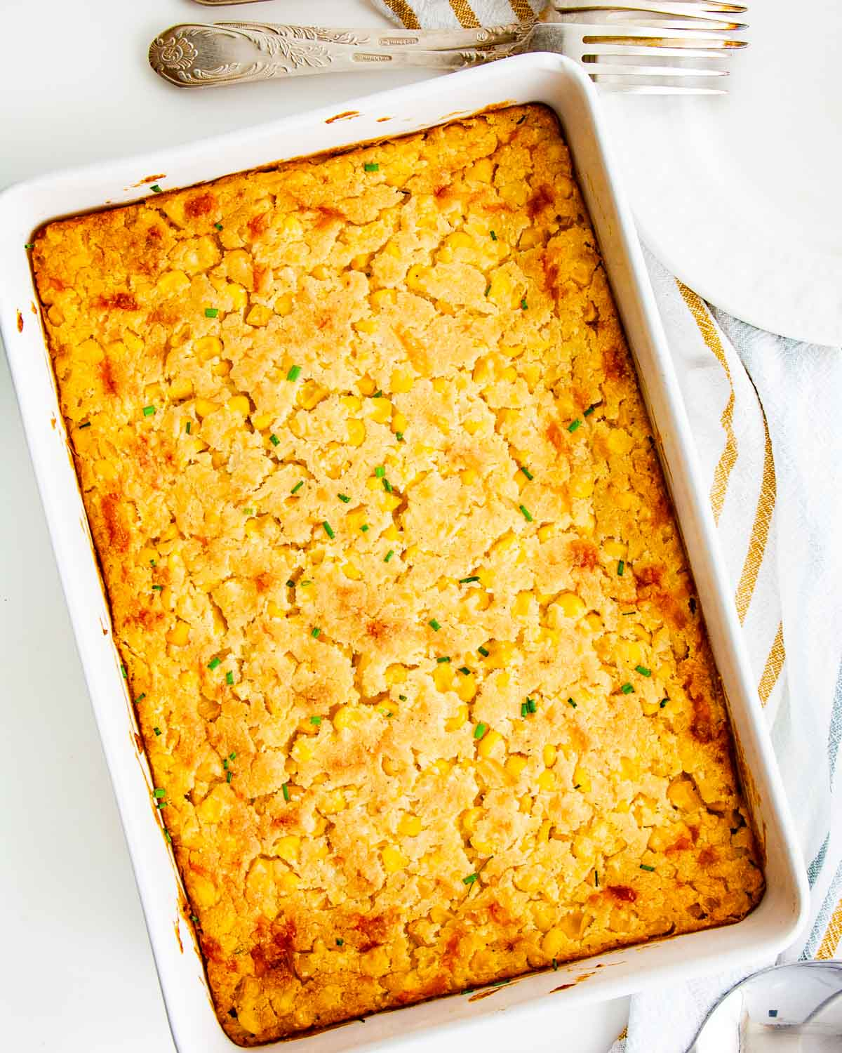 overhead shot of corn casserole in a white casserole dish.