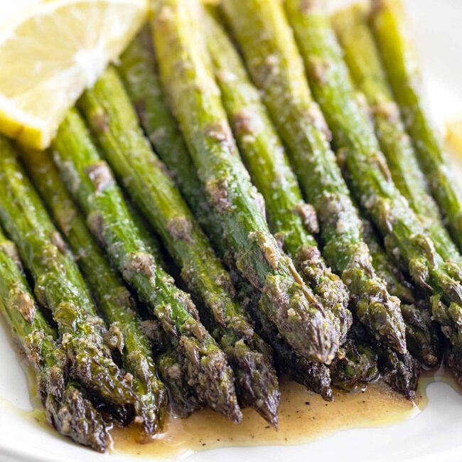 closeup of roasted asparagus on a plate with lemon wedge.