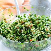 closeup of tabbouleh salad in a glass bowl with a spoon inside.