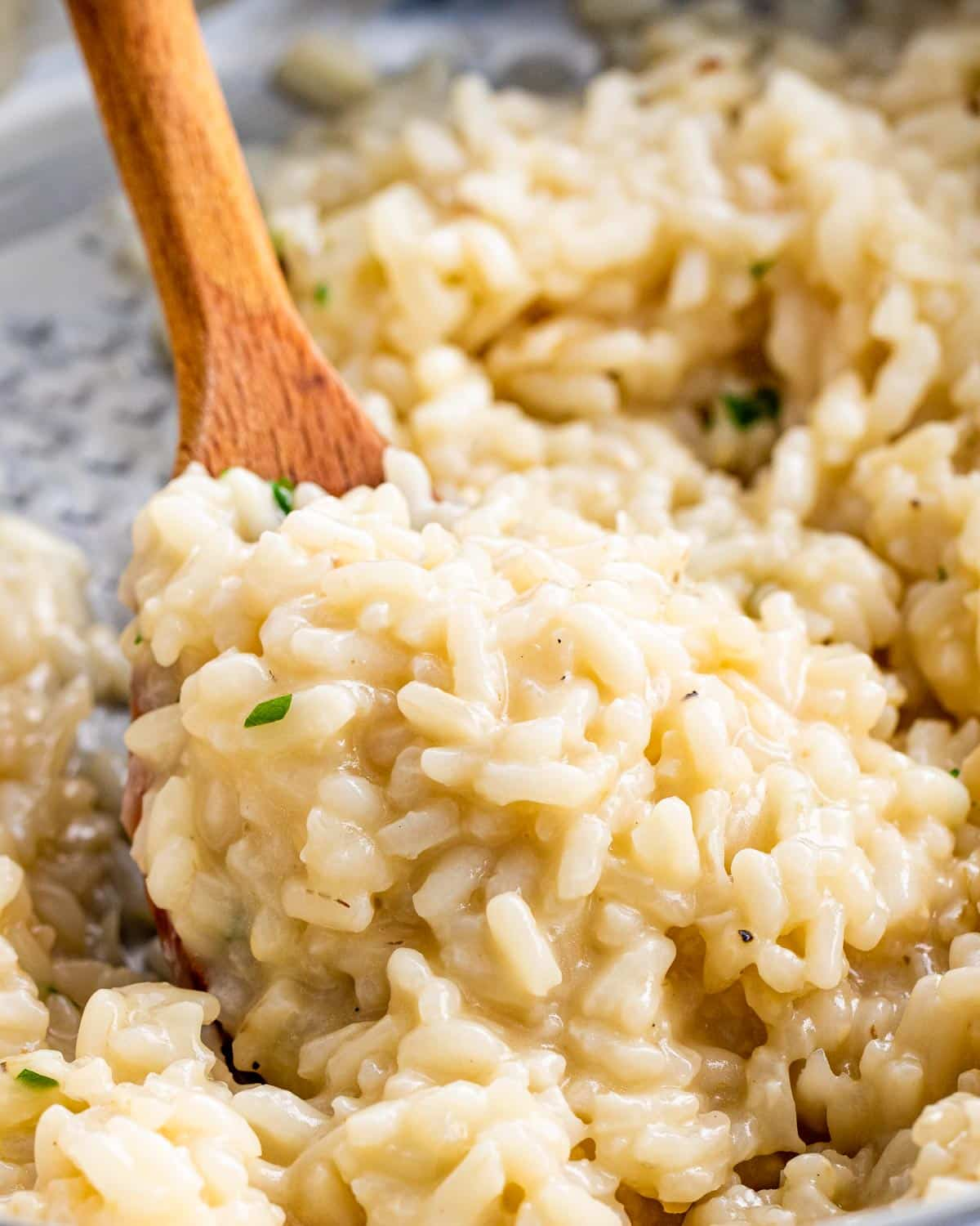 a wooden spoon holding some risotto in a pan.