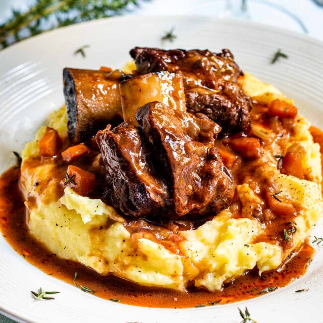 2 beef short ribs on a bed of mashed potatoes.