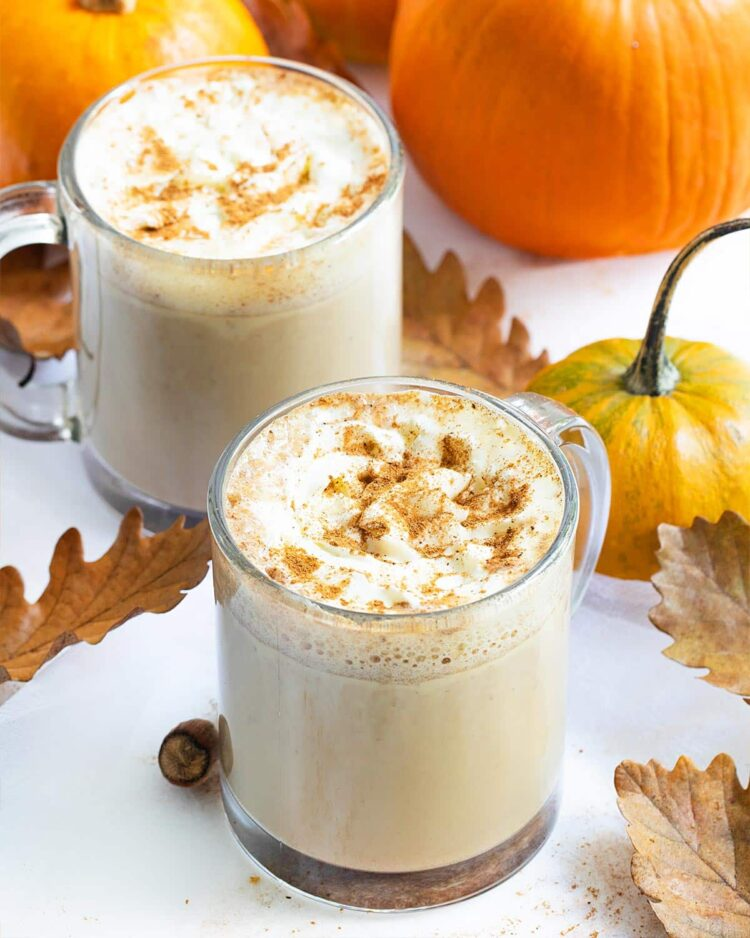 two cups filled with pumpkin spice latte.