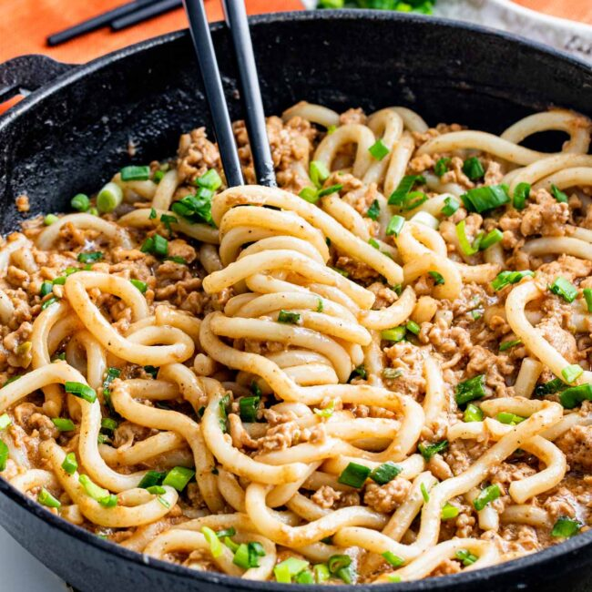 overhead of quick chicken peanut noodles in a skillet with chopsticks twirling some noodles.