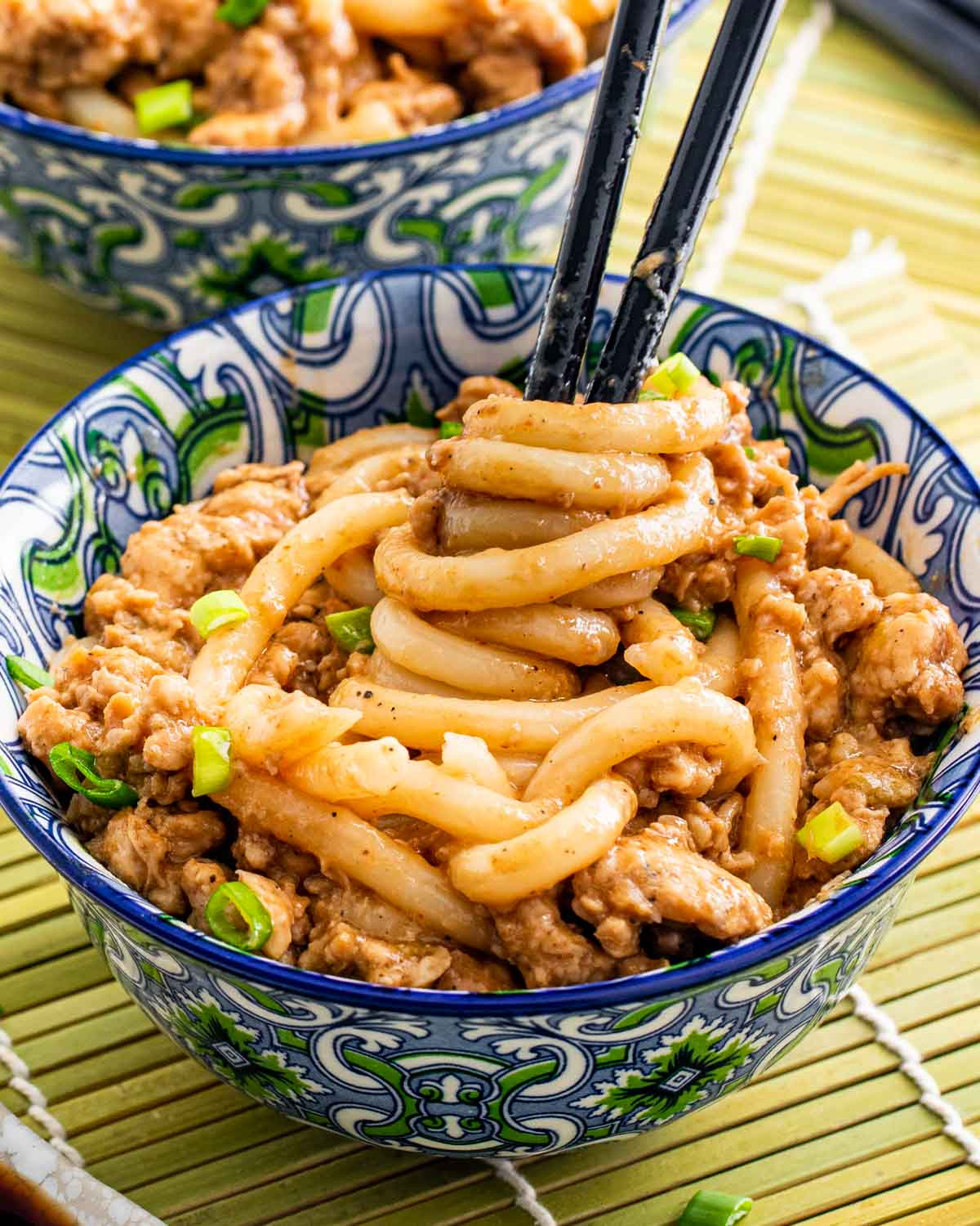 quick chicken peanut noodles in an asian bowl with chopsticks twirling some noodles.