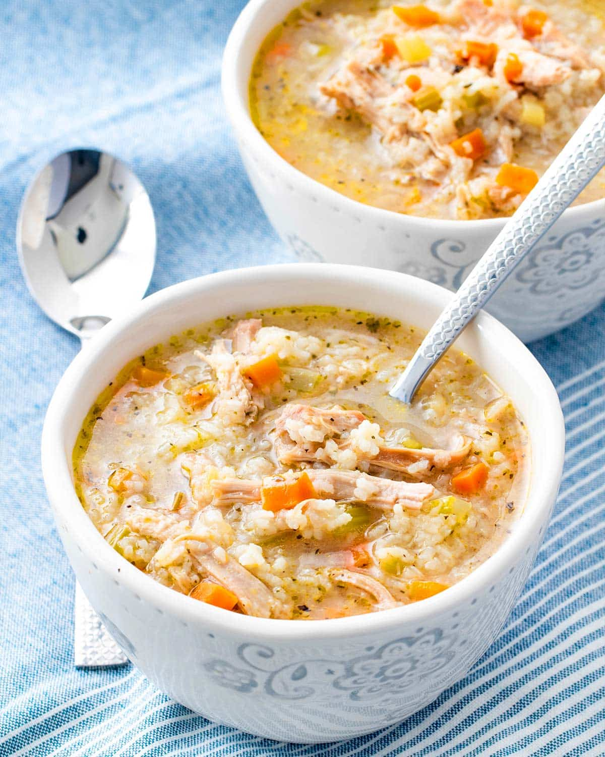a bowl of freshly made chicken and rice soup with a spoon in it.