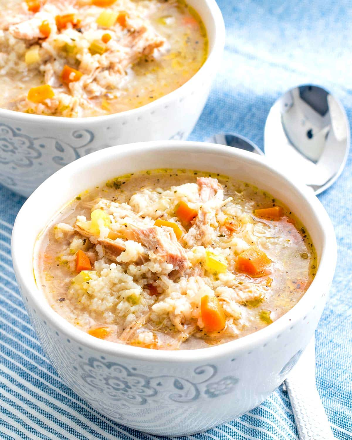 a white bowl with freshly made chicken and rice soup.