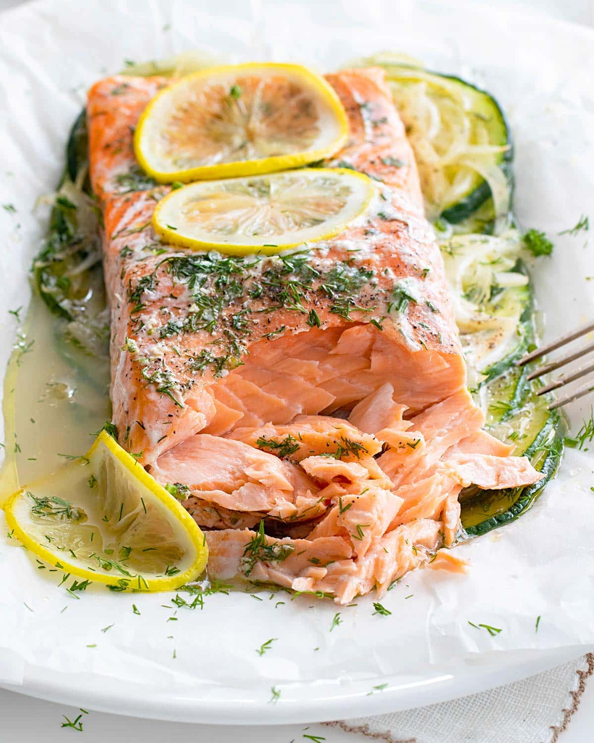 salmon en papillote on a plate flaked with a fork.