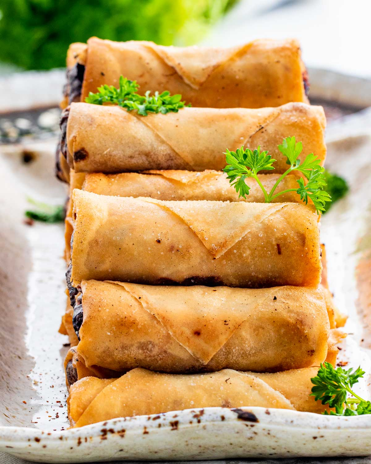 a bunch of freshly made spring rolls on a serving platter.