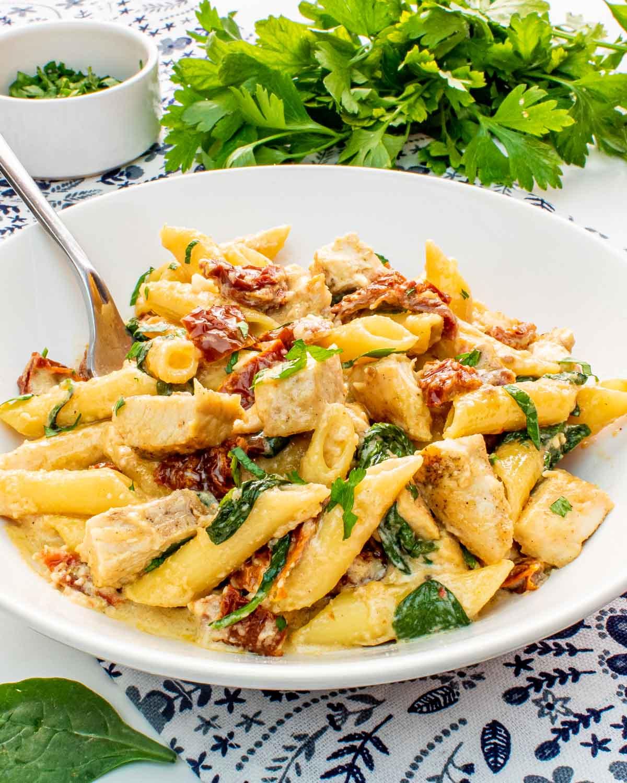 creamy tuscan chicken pasta in a white bowl.