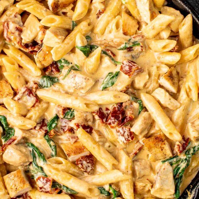 creamy tuscan chicken pasta in a black skillet.