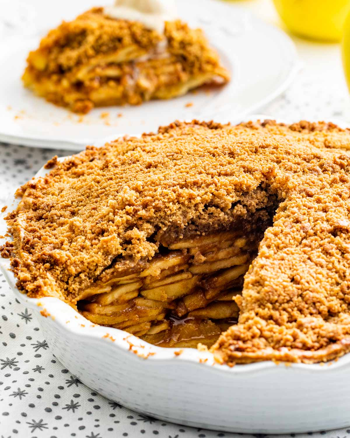 closeup of a dutch apple pie with a slice taken out of it.