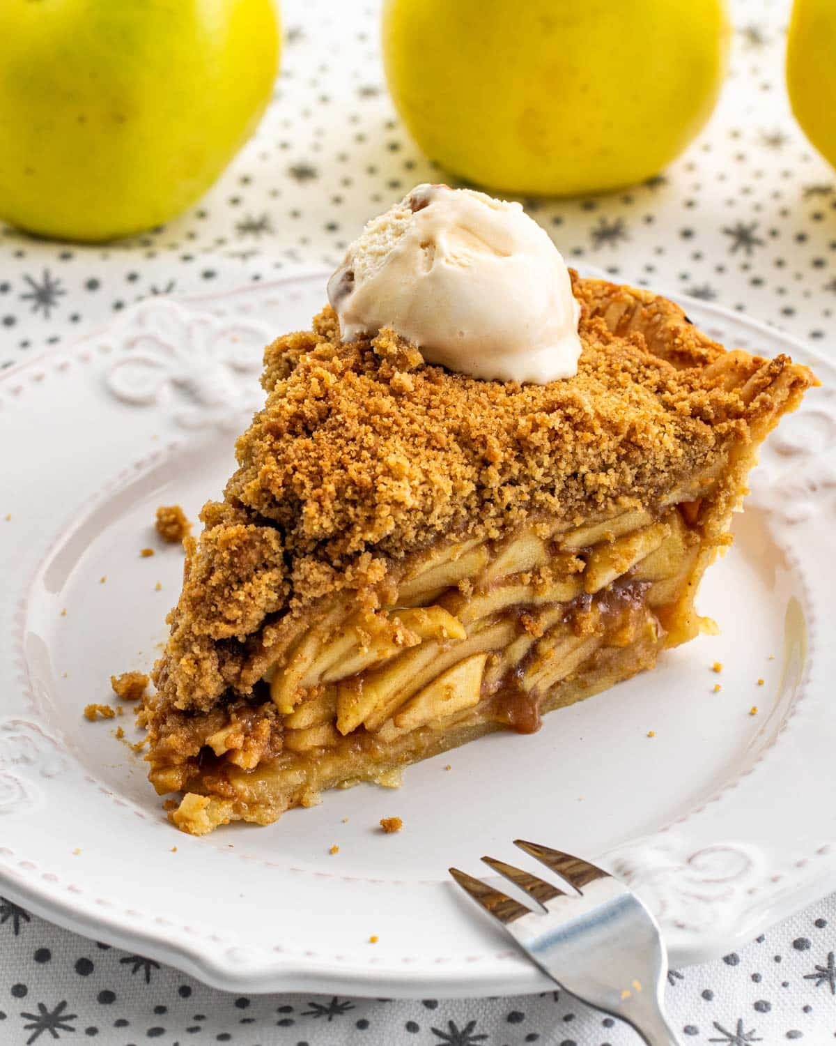 a gorgeous slice of dutch apple pie on a white plate.