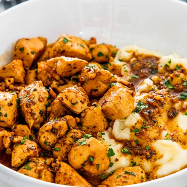garlic butter chicken bites in a white plate with mashed potatoes.