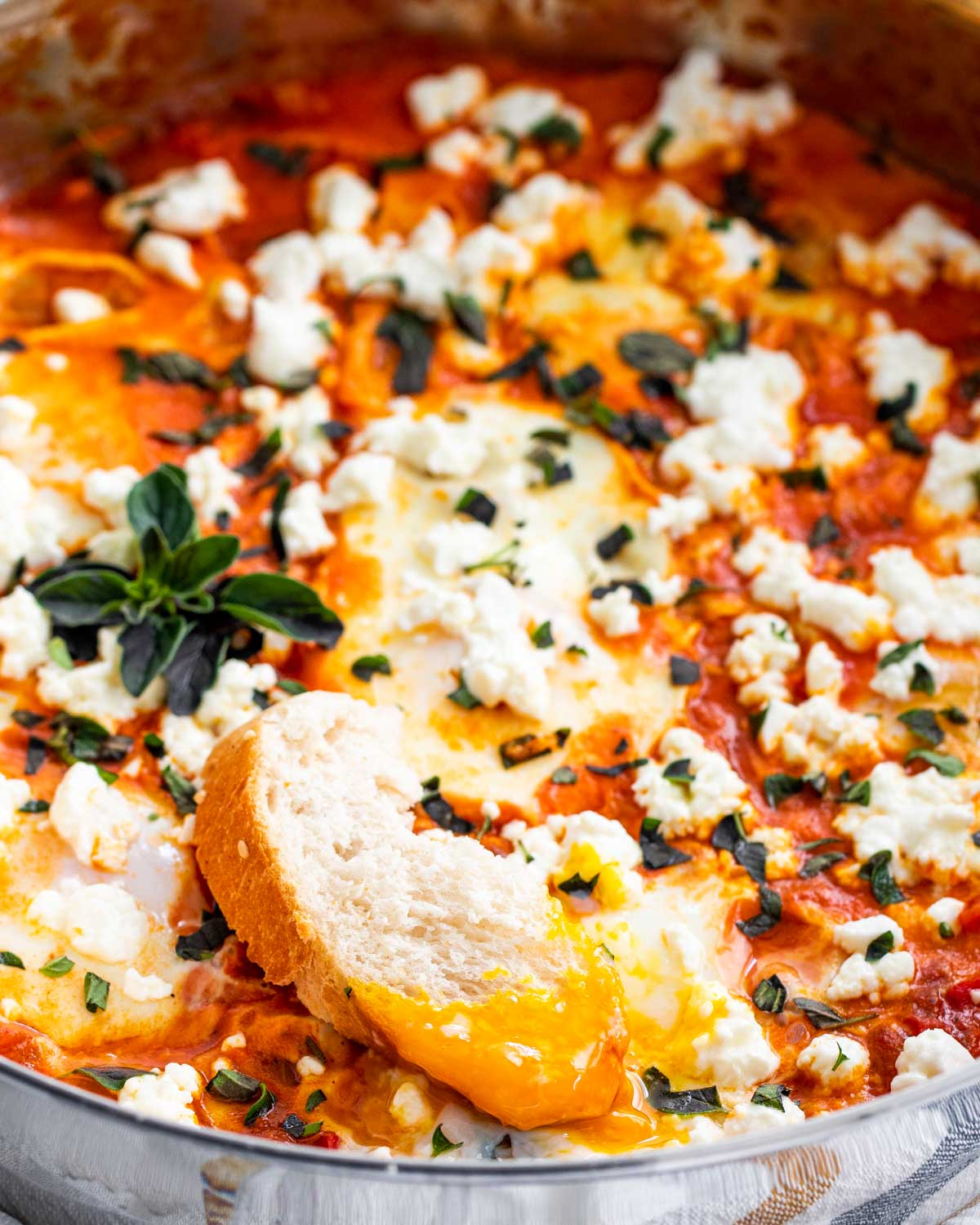 shakshuka in a skillet with a piece of bread dipped in an egg.
