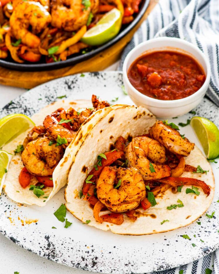 shrimp fajitas on a white plate with salsa in the background.