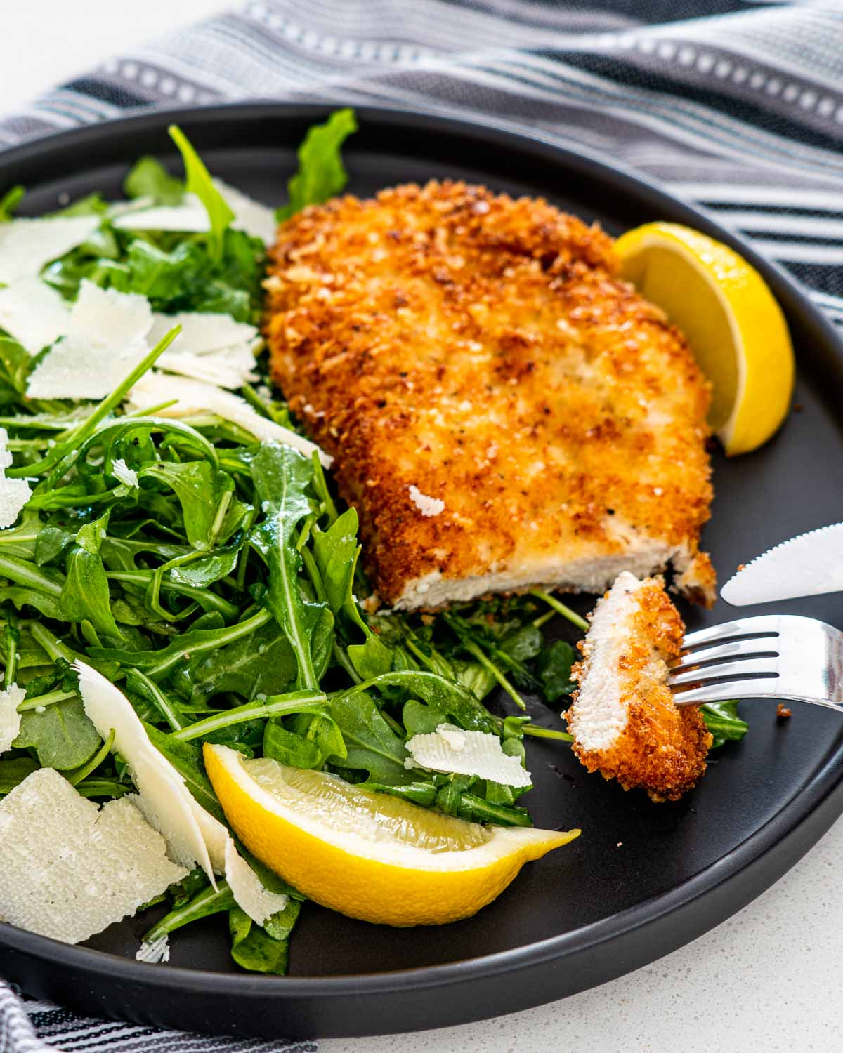 chicken milanese next to arugula salad garnished with shaved parmesan and lemon wedges.