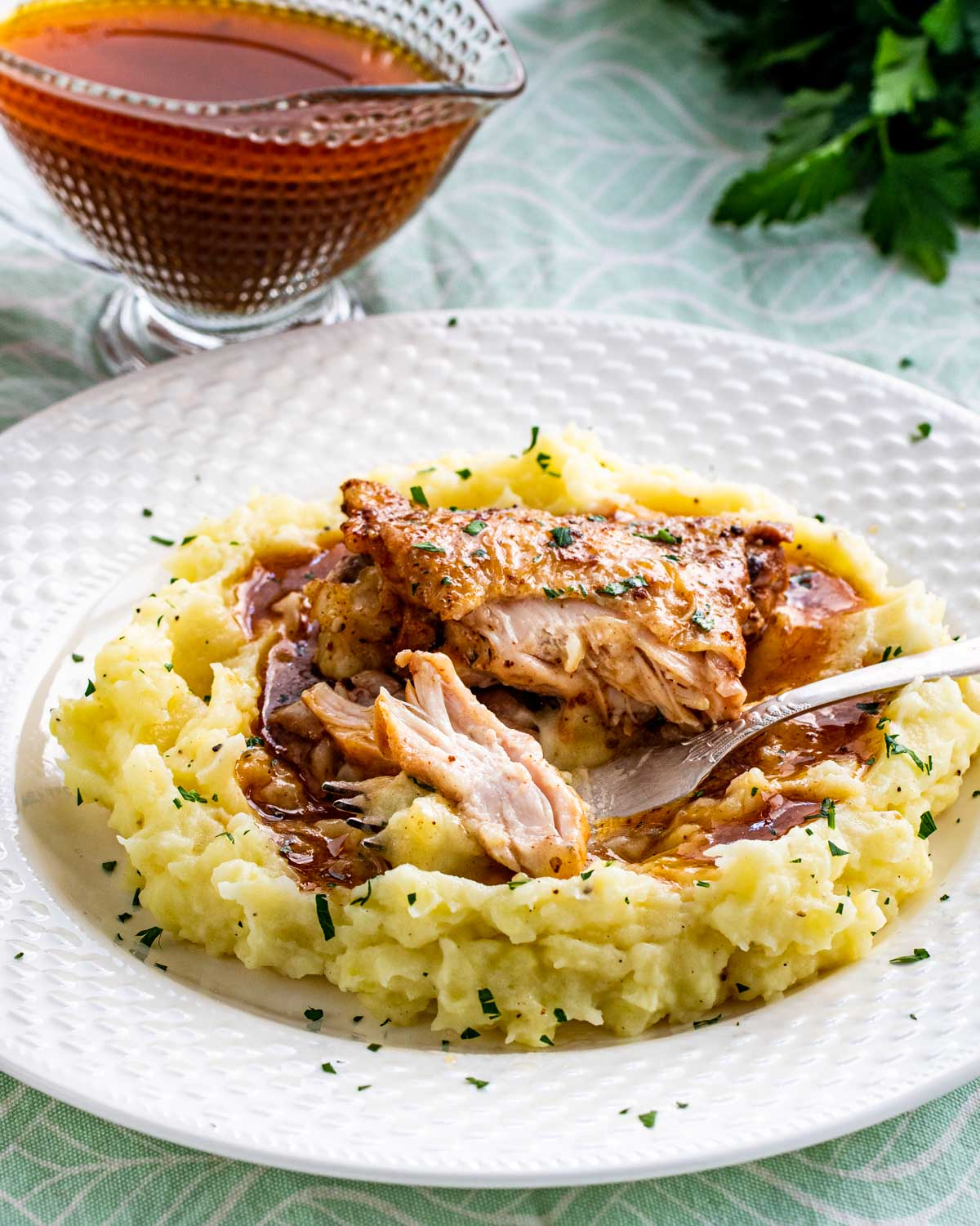chicken thigh with gravy on a bed of mashed potatoes.