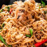 a pair of chopsticks lifting some thai drunken noodles from a bowl.