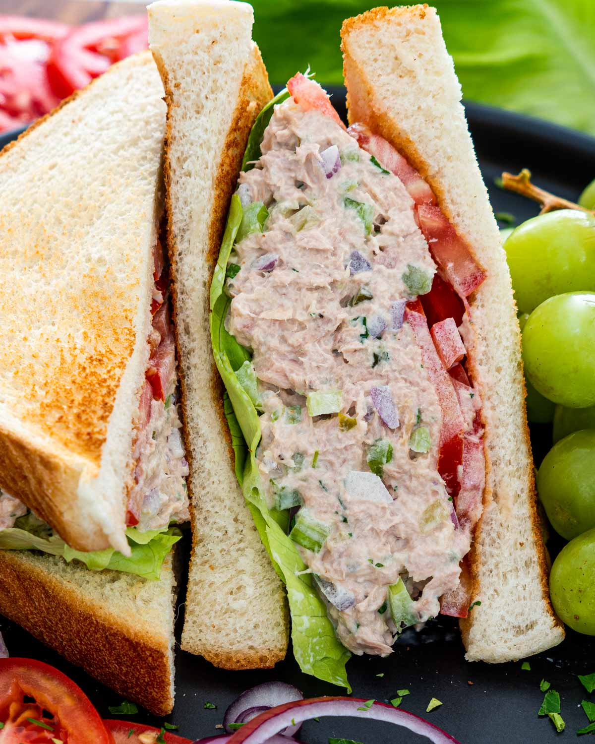 a tuna salad sandwich with lettuce and tomatoes.