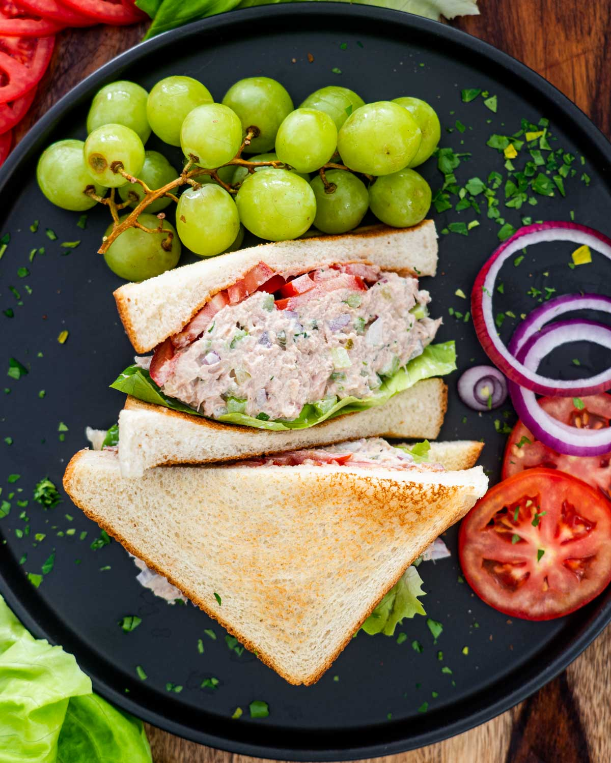 tuna salad sandwich with lettuce and tomatoes and grapes on the side on a black plate.