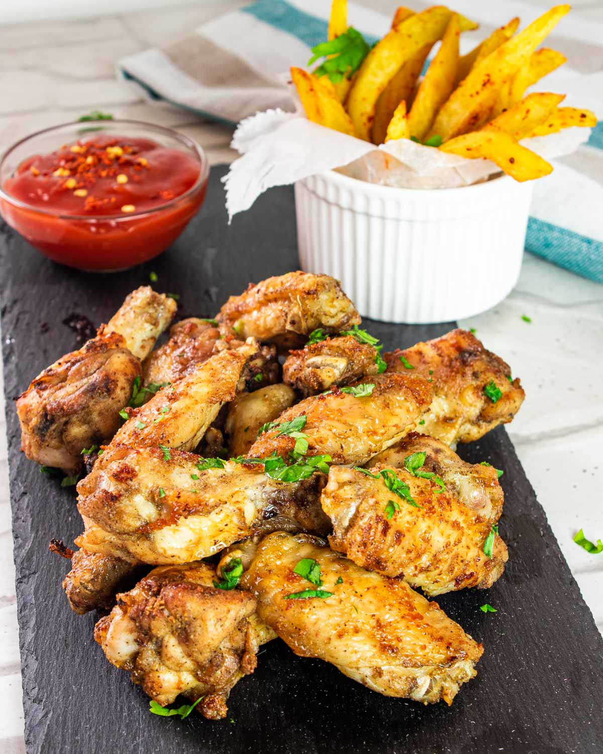 chicken wings on a black plate with french fries in the background.