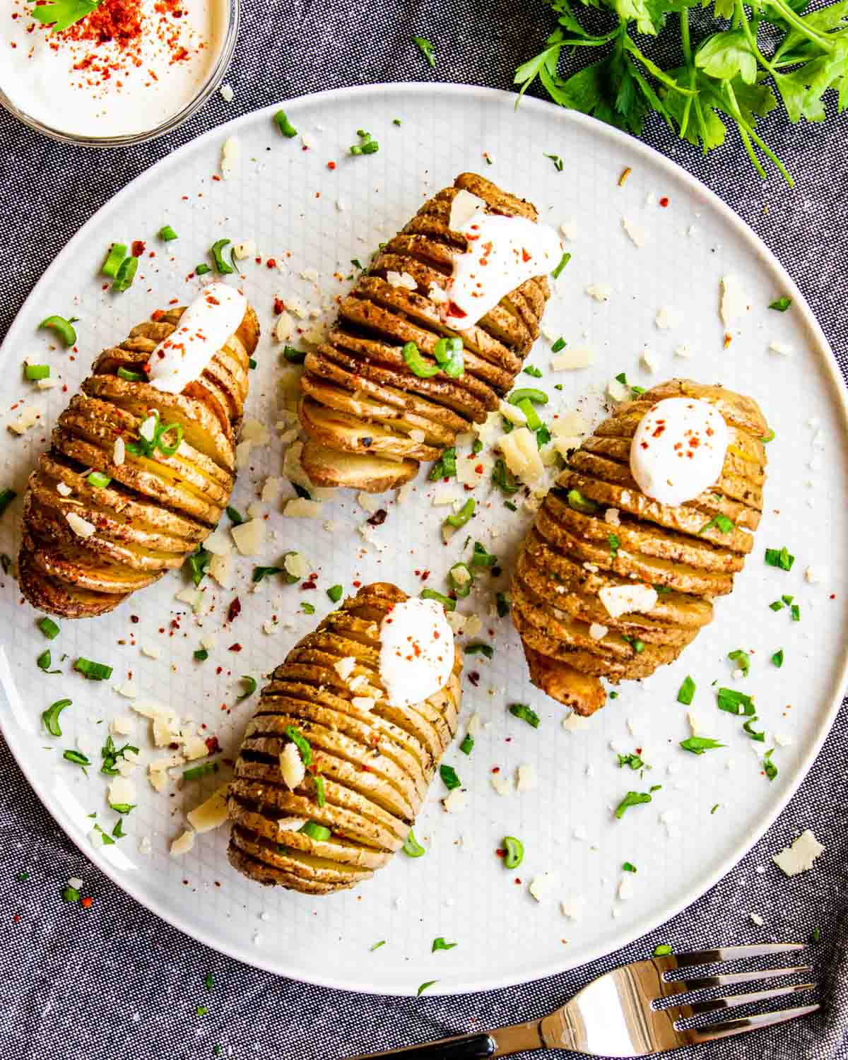 4 hasselback potatoes on a white plate with sour cream and parsley.